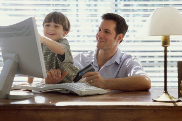 отец смотрит, как сын показывает что-то на мониторе