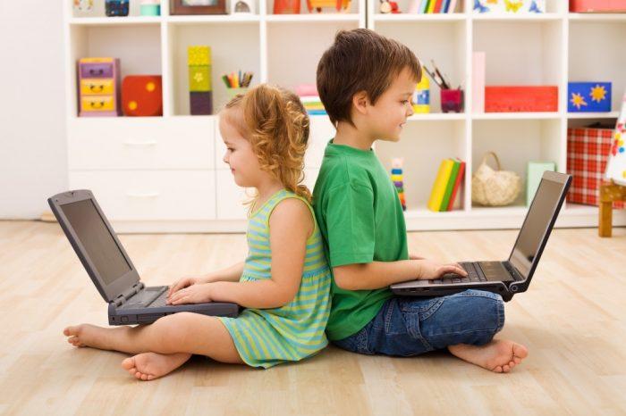 девочка с мальчиком сидят спина к спине с ноутбуками