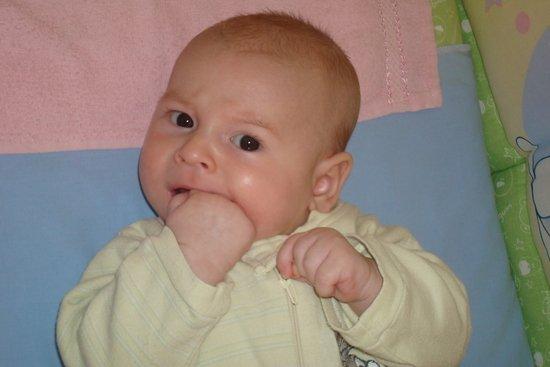 Младенец примерно двух месяцев сосёт свой кулак