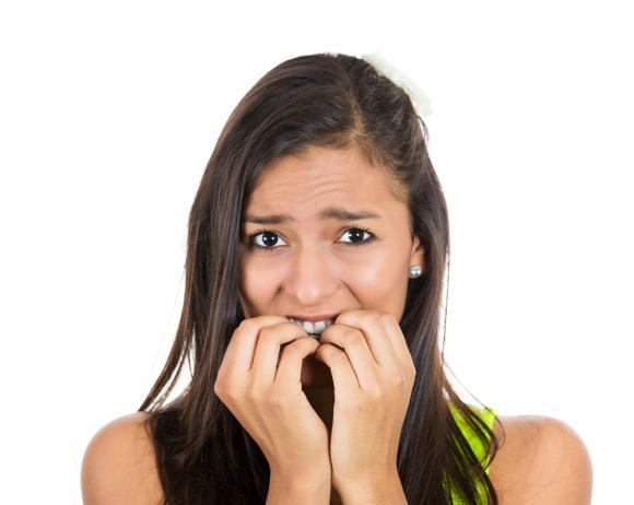 У девушки испуганный вид, она тянет пальцы в рот