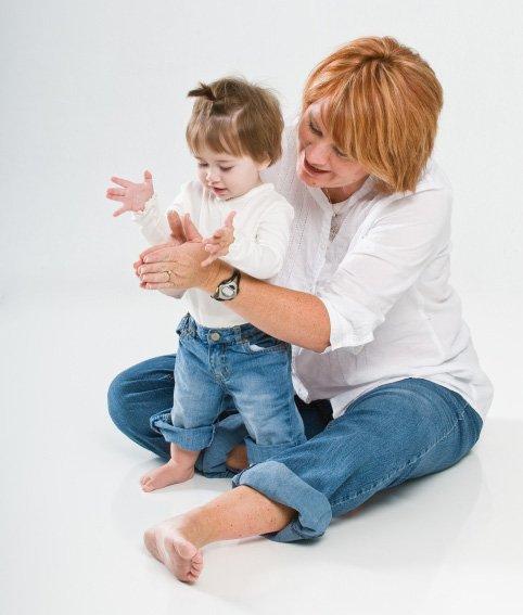 Мама показывает мальчику игру «Ладушки»