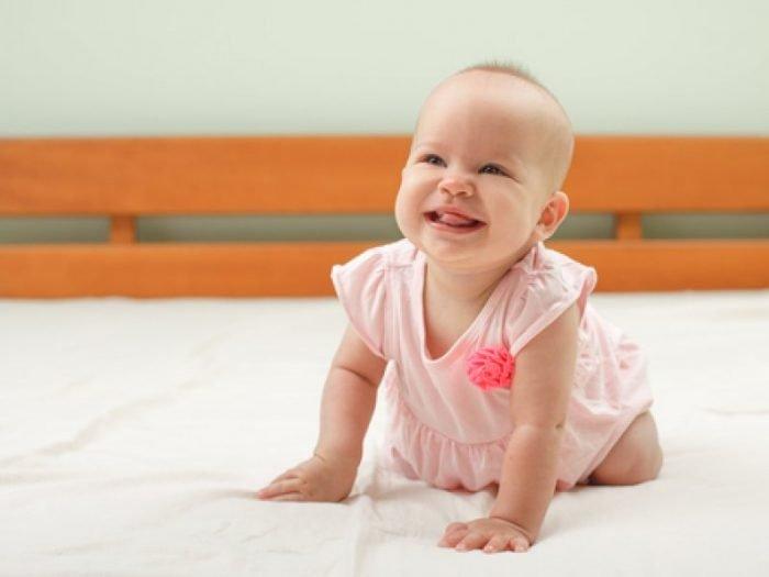 малышка в платьице стоит на четвереньках на мягкой подстилке