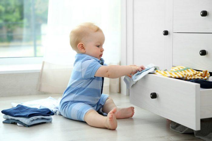 ребёнок сидит у открытого ящика с вещами и держит в руках одежду