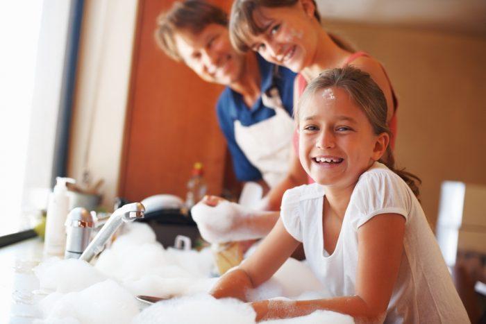 девочка у раковины в куче пены, позади родители
