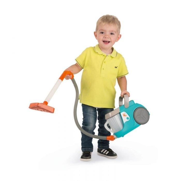 мальчик стоит с пылесосом в руках