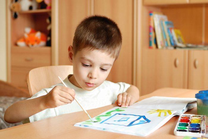 мальчик рисует картинку кисточкой и красками