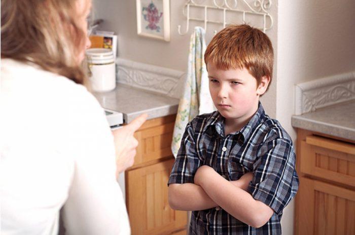 женщина тычет пальцем в насупившегося мальчика