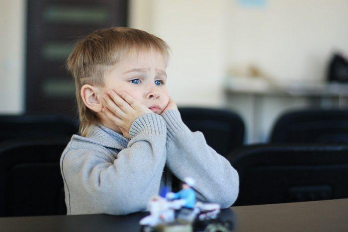 Ребёнок сидит за столом и скучает