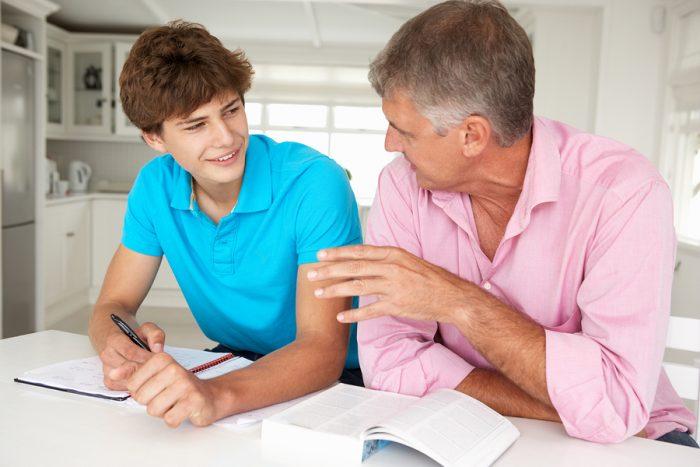 отец говорит с подростком, сидя за столом