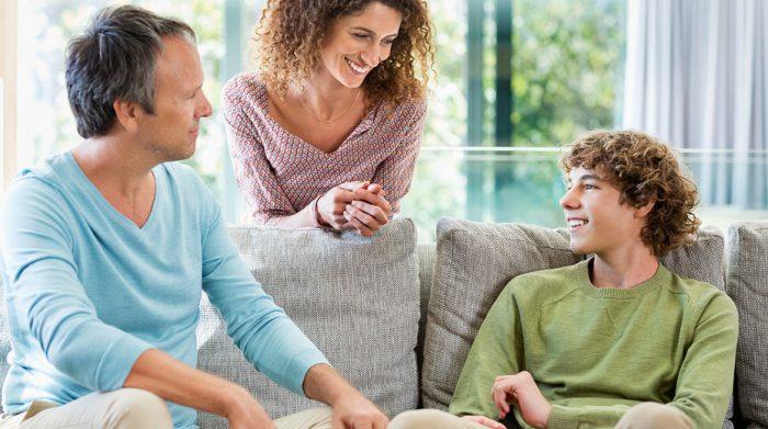 родители улыбаются, глядя на сына