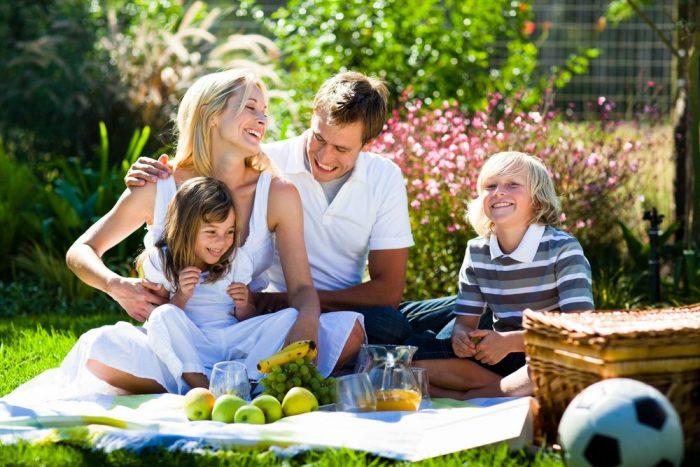 Улыбающиеся папа, мама, дочка и сын на пикнике