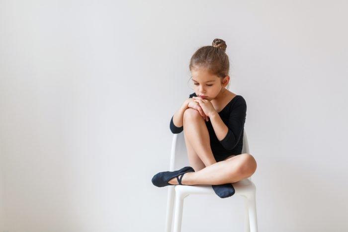 Грустная девочка сидит на стуле
