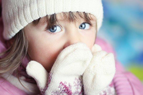 Девочка прикрывает нос варежками