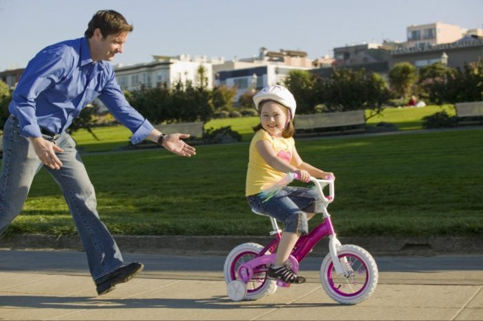 Девочка едет на велосипеде, а за ней бежит папа