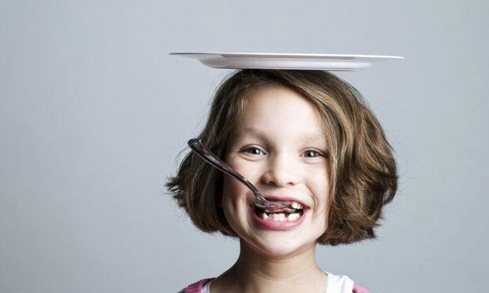 Девочка с тарелкой на голове и ложкой во рту