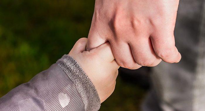 Рука ребёнка, держащегося за руку взрослого