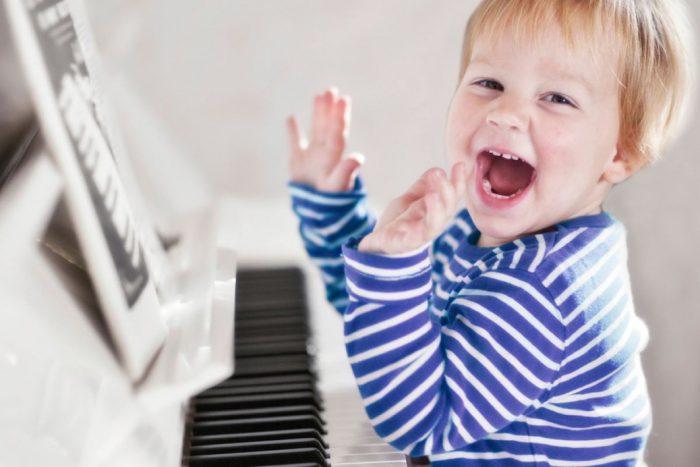 Маленький мальчик смеётся сидя за пианино