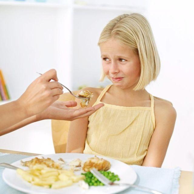 Мама кормит дочь из ложки