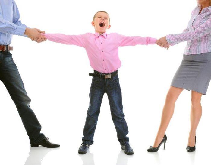 Родители тянут сына за руки в разные стороны