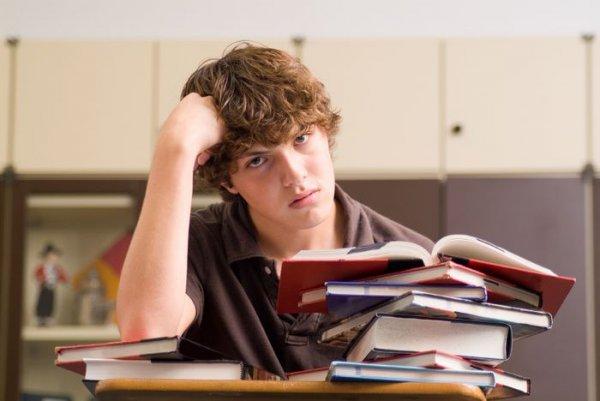Подросток сидит над учебниками