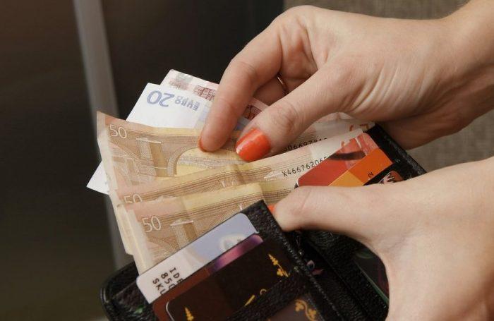 Женщина держит кошелёк с деньгами