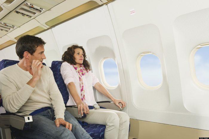 Женщина испуганно держится за кресло в салоне самолёта