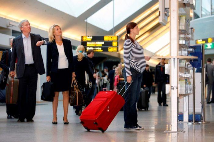 Беременная стоит в зале аэропорта