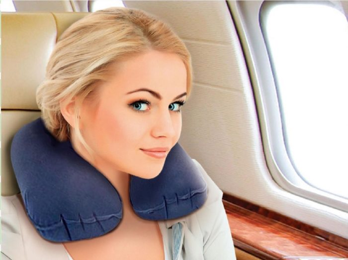 Женщина сидит в самолёте с подушкой под голову