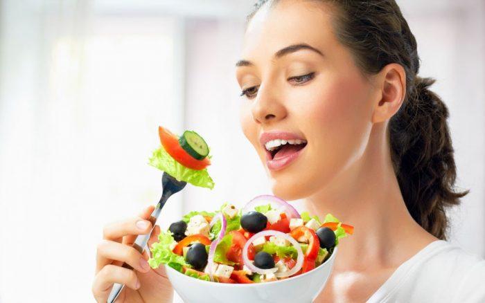 девушка держит в руке тарелку с овощным салатом
