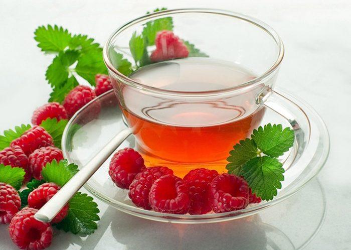 чай в чашке, рядом ягоды малины