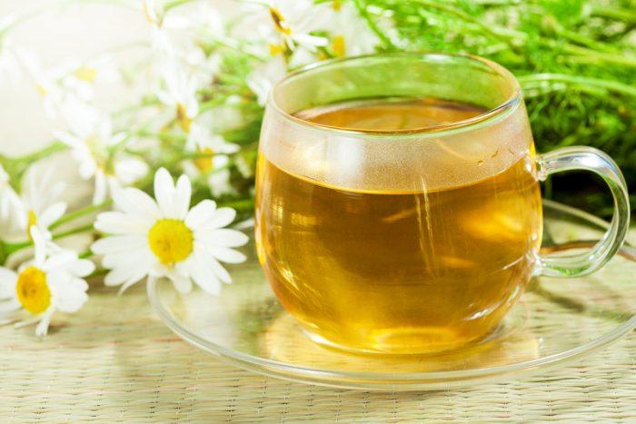 чай в чашке, рядом цветки ромашки