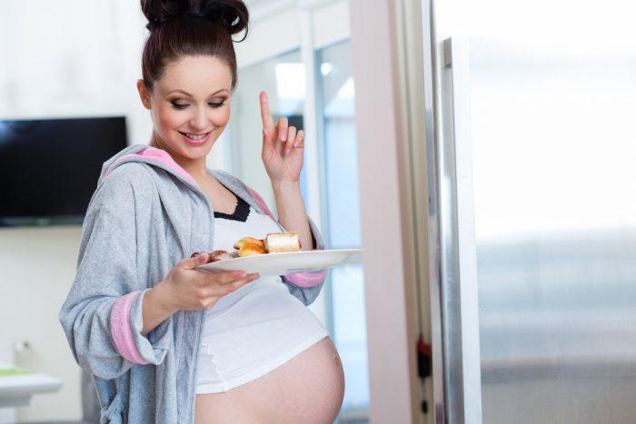 беременная держит тарелку с выпечкой