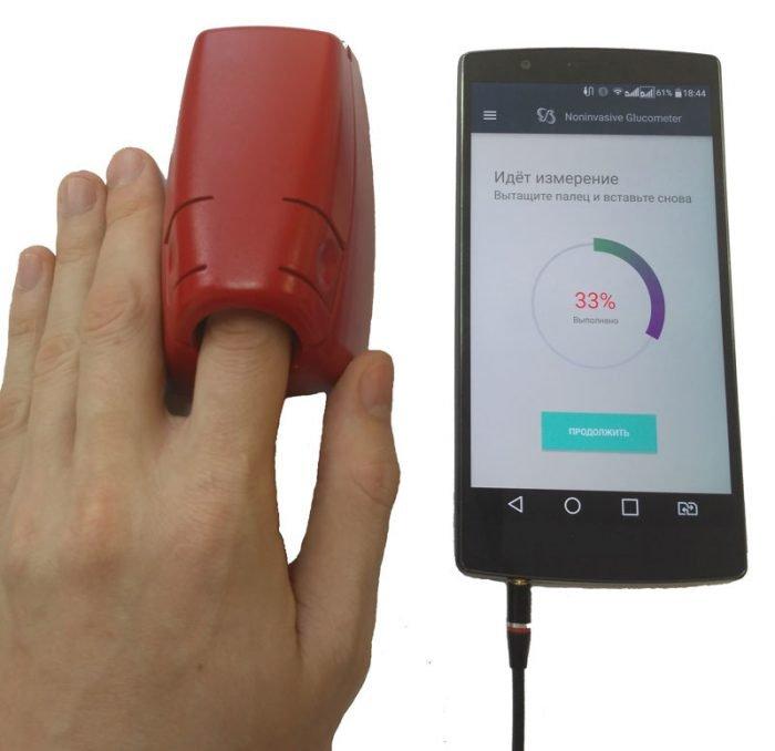 глюкометр с пальцем, вставленным в аппарат