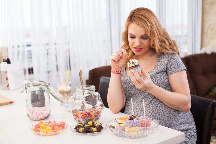 Беременная сидит за столом со сладостями и держит в руке пирожное
