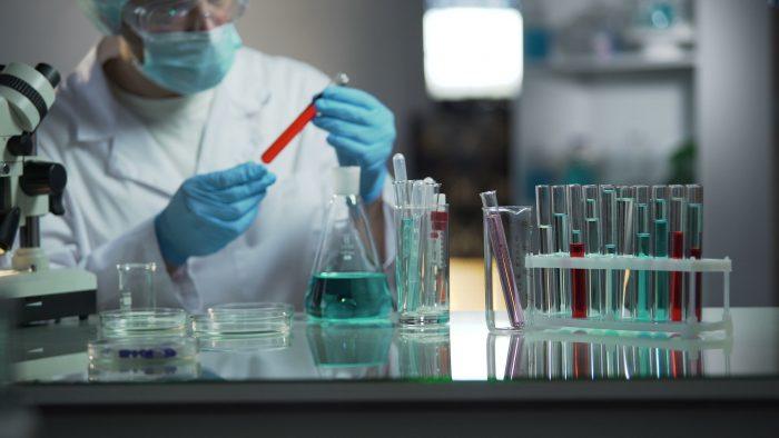 Врач изучает пробирки с кровью в лаборатории