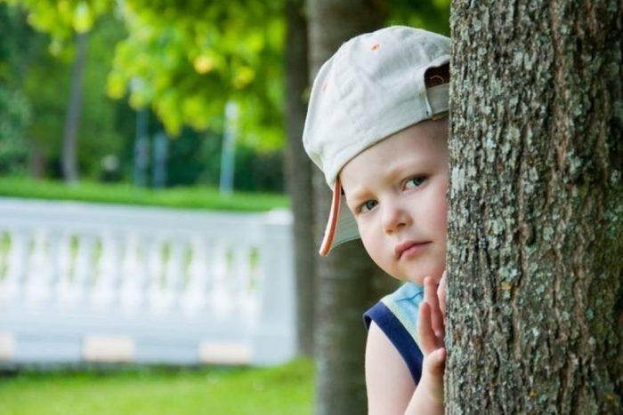 Мальчик прячется за деревом и испуганно выглядывает оттуда