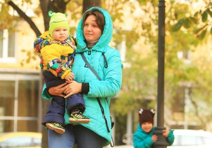 женщина несёт на руках ребёнка