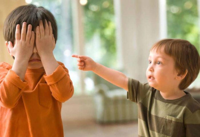 Один мальчик закрыл лицо руками, другой показывает на него пальцем