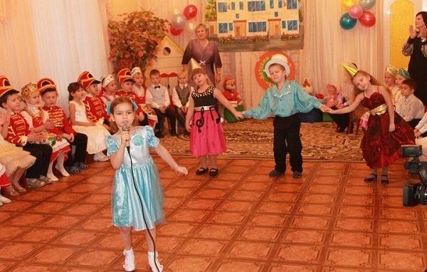Девочка-дошкольница одна поёт песню в микрофон на утреннике в детском саду