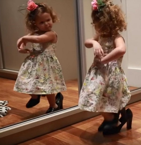 Маленькая девочка танцует перед зеркалом в маминых туфлях