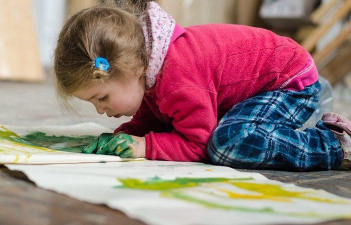 Маленькая девочка увлечённо рисует на обоях сидя на полу Ребёнок, склонный к живописи, обычно спокойный, усидчивый, за любимым занятием может проводить много времени