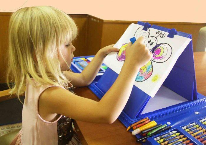 5. Девочка рисует на мольберте в наборе юного художника