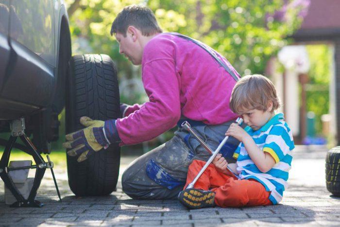 Папа меняет колесо на машине, маленький сын сидит рядом и держит инструменты