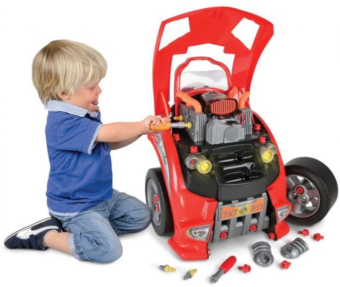 Мальчик чинит разобранную игрушечную машину