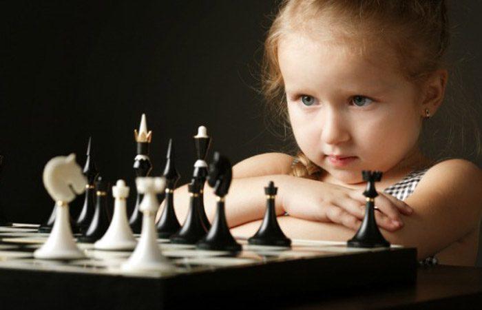 Девочка смотрит на шахматную доску