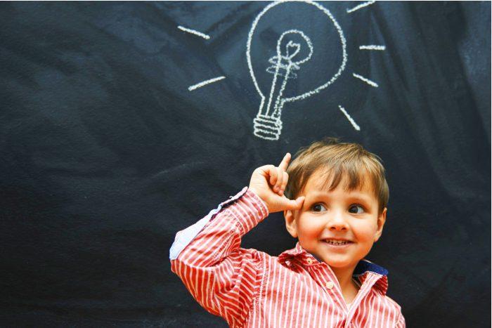 На доске мелом изображена светящаяся лампочка; мальчик о чём-то думает и держит вверх указательный палец