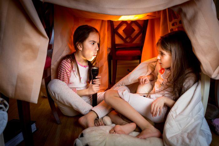 Девочки сидят под столом в импровизированном домике и пугают друг друга