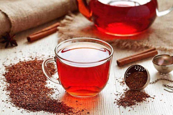 чашка чая ройбуш с россыпью сухой смеси на столе