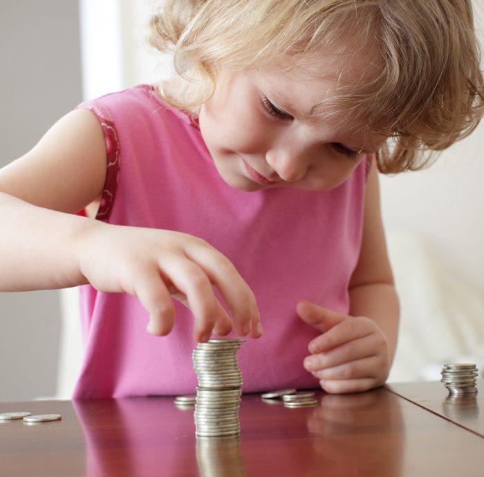 Девочка складывает монетки