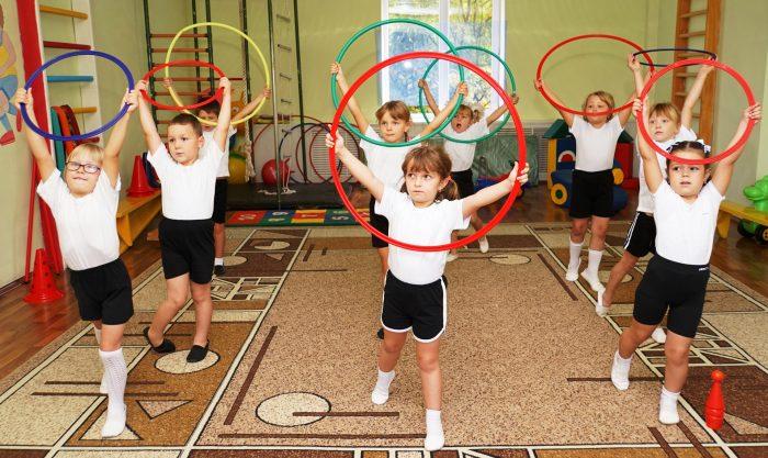 Дети делают упражнения с обручами